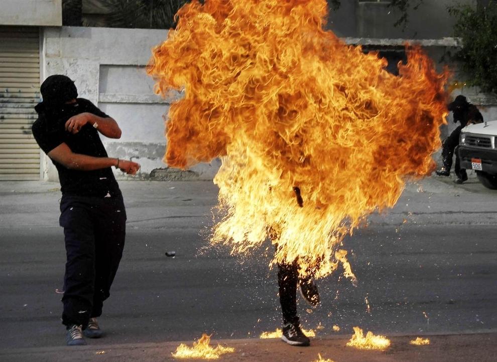 Một người biểu tình chống chính phủ tại Bahrain chìm trong lửa sau khi cảnh sát chống bạo động bắn vào bom xăng trong tay người này khi người này chuẩn bị ném về phía cảnh sát