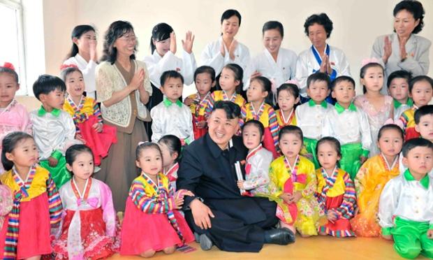 Nhà lãnh đạo Kim Jong-un ngồi chụp ảnh chung với trẻ em trong chuyến thăm tới nhà máy cơ khí ở Triều Tiên.