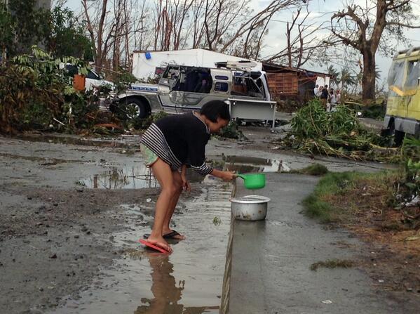 Một bé gái múc nước mưa trên đường, trong khi nhiều người dân sống trong cảnh đói khát tại thành phố Tacloban.