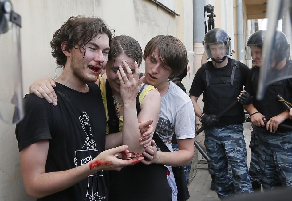 Cảnh sát chống bạo động đang bảo vệ các nhà hoạt động vì quyền đồng tính, những người này đã bị đánh đập bởi những người biểu tình chống người đồng tính trong một cuộc biểu tình về quyền đồng tính ở St.Petersburg, Nga.