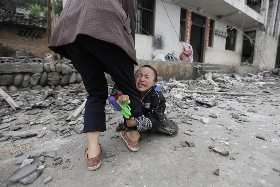 Một cậu bé ôm chân mẹ than khóc trước ngôi nhà bị động đất tàn phá hư hại. Rrận động đất cường độ 6,6 độ richter xảy ra tại làng Long Môn, quận Lộc Sơn, tỉnh Tứ Xuyên.