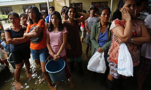 Mọi người đứng chờ nhận thực phẩm cứu trợ tại một trung tâm sơ tán lũ lụt ở Calumpit, Philippines.