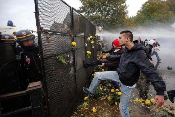 Người biểu tình đạp hàng rào, trong khi cảnh sát dùng vòi rồng để phun nước giải tán người biểu tình ở Quimper, Pháp.