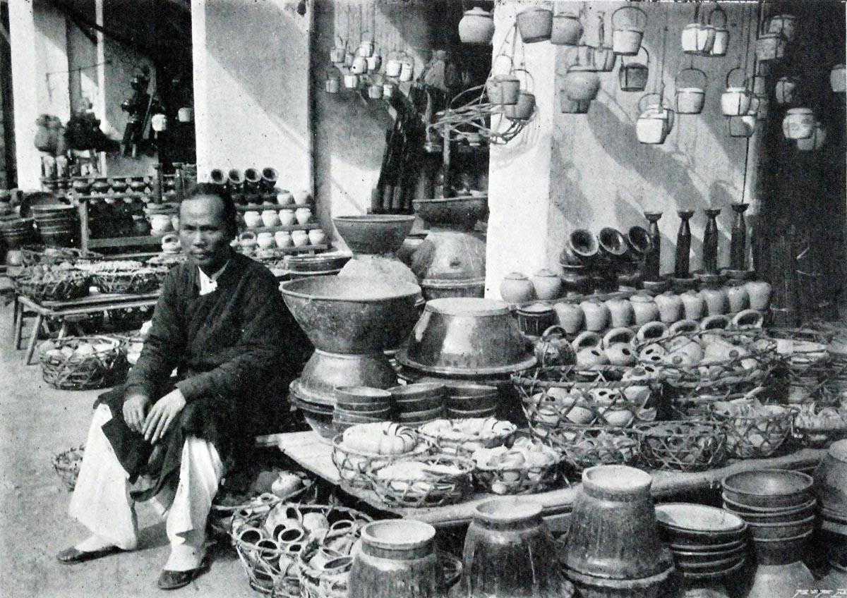 Một ông chủ quầy gốm bên cửa hàng của mình.