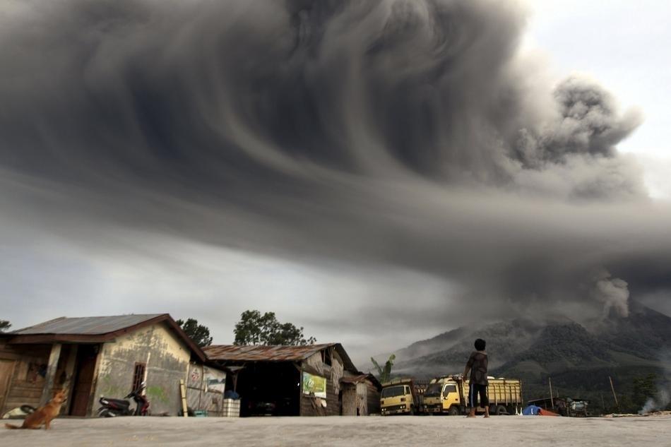 Một đứa trẻ đang xem cảnh ngọn núi Sinabung ở phía Tây Indonesia phun trào. Vụ phun trào này đã khiến gần 6.000 người sống quanh chân núi phải đi sơ tán.