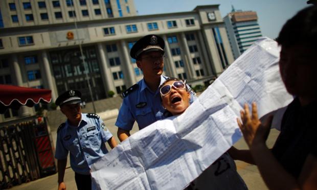 Cảnh sát cưỡng chế một người biểu tình khỏi khu vực trước tòa án nhân dân Tế Nam, Trung Quốc, nơi sẽ xét xử vụ án Bạc Hy Lai vào ngày hôm nay.