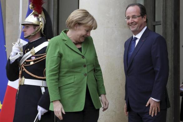 Tổng thống Pháp Francois Hollande chào đón Thủ tướng Đức Angela Merkel khi bà tới thăm Cung điện Elysee ở Paris.