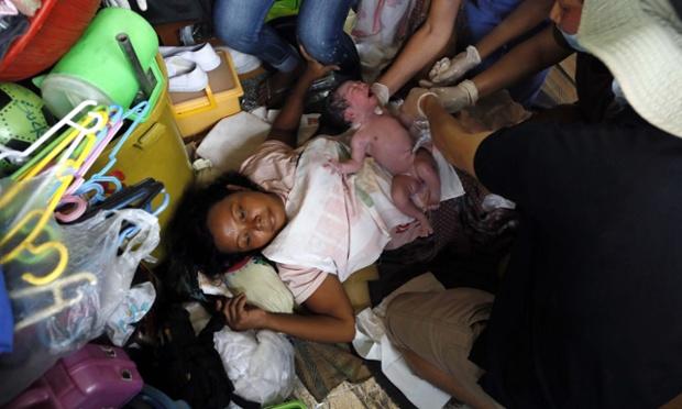 Các nhân viên y tế hỗ trợ một nạn nhân sống sót sau siêu bão Haiyan sinh con trong lều tạm tại thành phố Tacloban, Philippines.