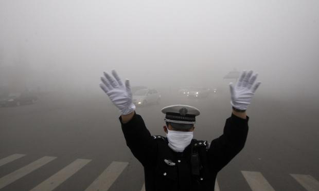 Một cảnh sát ra hiệu chỉ dẫn giao thông trên đường phố bao phủ đầy sương mù ở thành phố Cáp Nhĩ Tân, Trung Quốc.
