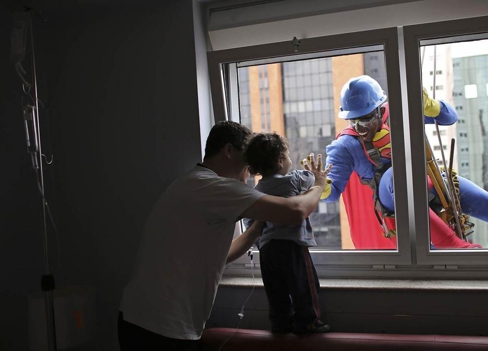 Một người đàn ông ăn mặc như Superman mỉm cười với bệnh nhân Joao Bertola, 2 tuổi, và cha của cậu bé tại Bệnh viện Infantil Sabara ở Sao Paulo, Brazil.