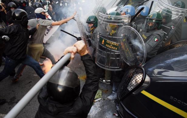 Cảnh sát chống bạo động đụng độ với người biểu tình trước tòa nhà Bộ Tài chính ở Rome, Italia.