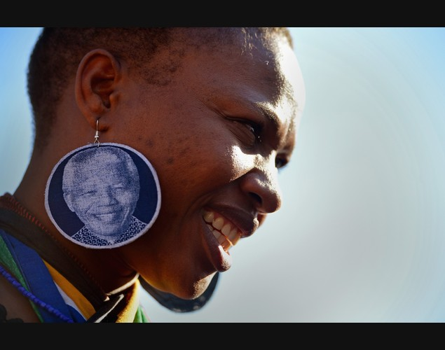 Một phụ nữ đeo khuyên tai có hình nhà lãnh đạo Nelson Mandela cùng những người khác cầu nguyện cho ông bên ngoài bệnh viện Pretoria, Nam Phi.