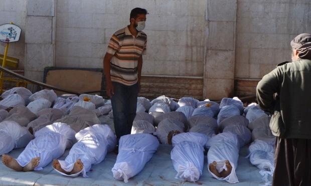Các nhà hoạt động Syria kiểm tra các thi thể của nạn nhân thiệt mạng trong một vụ tấn công của quân chính phủ ở Ghouta, Syria.