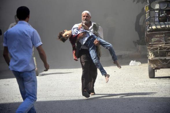 Một người đàn ông bế một cậu bé bé bị thương trong cuộc không kích bất ngờ của quân đội chính phủ vào lực lượng quân đội Syria tự do tại thành phố Damascus, Syria.