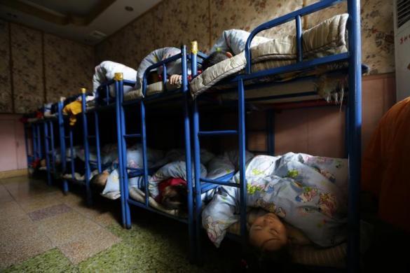 Trẻ em ngủ trong khu ký túc xá tại một trường mầm non dành cho con của công nhân nhập cư ở ngoại ô Bắc Kinh, Trung Quốc.