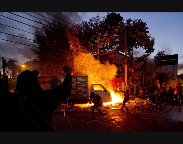 Người biểu tình la hét, ném đá vào cảnh sát chống bạo động và đốt xe ô tô ở Belo Horizonte, Brazil.