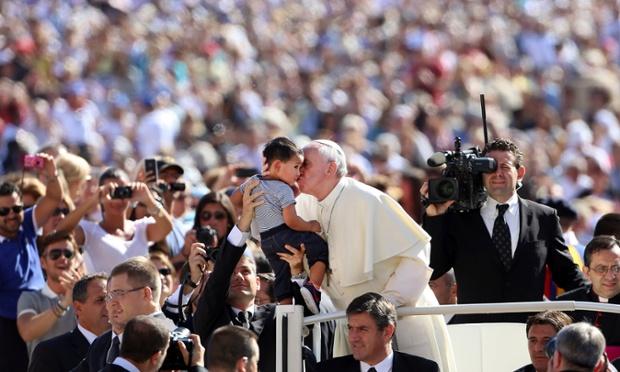 Giáo hoàng Francis hôn một em bé trước khi thực hiện bài phát biểu hàng tuần tại quảng trường St. Peter ở thành phố Vatican.