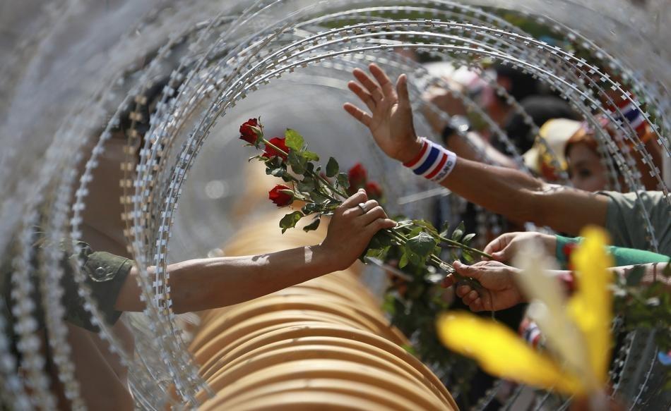 Một người biểu tình chống chính phủ đã tặng hoa hồng đỏ cho một người lính Thái Lan tại Bộ Quốc phòng trong một cuộc biểu tình ở Bangkok.