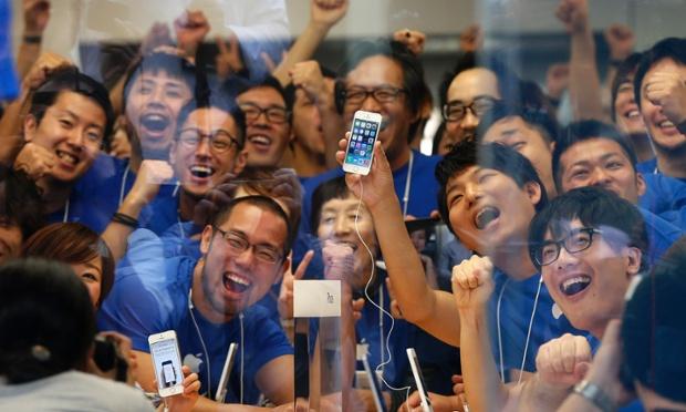 Các nhân viên của cửa hàng chụp ảnh với iPhone 5S trước khi bán tại một cửa hàng Apple ở Tokyo, Nhật Bản.