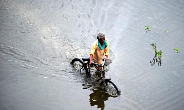 Một người đàn ông dắt xe đạp trên đường phố ngập lụt ở Allahabad, Ấn Độ.