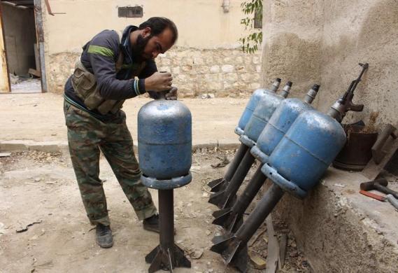 Một chiến binh phiến quân đang lắp ráp những quả rocket tự chế từ vỏ bình gas tại thành phố Aleppo, Syria.