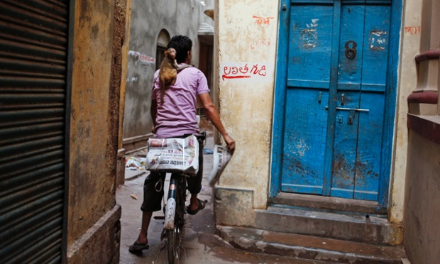 Một người bán báo dạo mang theo khỉ trên vai, đạp xe qua một ngõ nhỏ ở Varanasi, Ấn Độ.