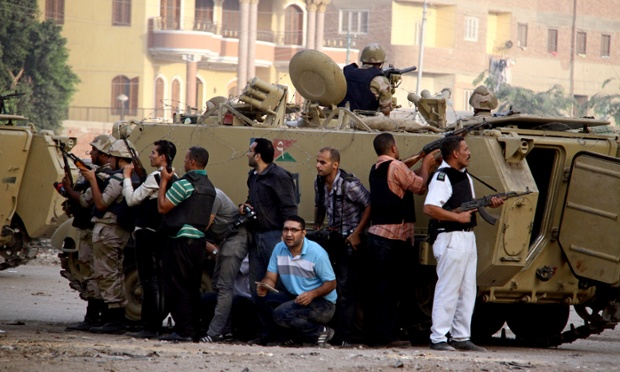 Lực lượng an ninh Hi Lạp đứng sau những chiếc xe bọc thép trong khi giao tranh với các phần tử Hồi giáo cực đoan ở Kerdasa.