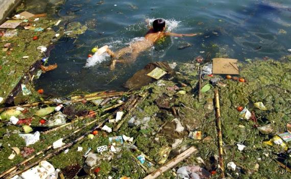 Một cậu bé đang bơi trong hồ chứa nước ô nhiễm tại tỉnh Quý Châu, Tây Nam Trung Quốc tháng 12/2006