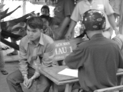 Lê Bảo Khanh (người bị còng tay) đang chờ cán bộ Công an phường 6 lập biên bản vi phạm tại hiện trường. (Ảnh: Cà mau online)