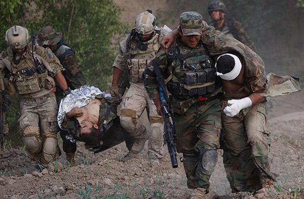 Một lính cứu thương đường không và một lính SEAL di chuyển một lính Afghanistan bị thương sau khi giao tranh với Taliban