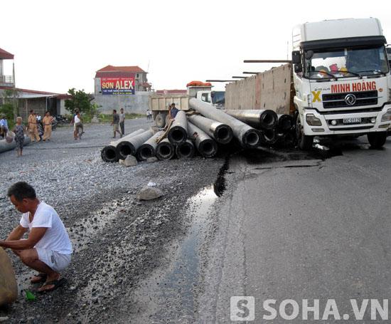Hàng chục chiếc ống bê tông trên xe bị đứt xích và trút xuống lòng đường.