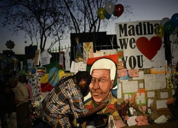 Một người dân Nam Phi sửa sang lại bức chân dung của Nelson Mandela đặt bên ngoài tường rào bệnh viện Medi Clinic tại Pretoria, nơi Nelson Mandela nằm điều trị 3 tuần qua.