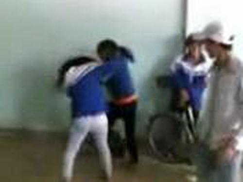 Hai nữ sinh vừa đánh nhau vừa văng ra những lời tục tĩu trong khi những học sinh khác đứng ngoài cổ vũ. Ảnh cắt từ video.