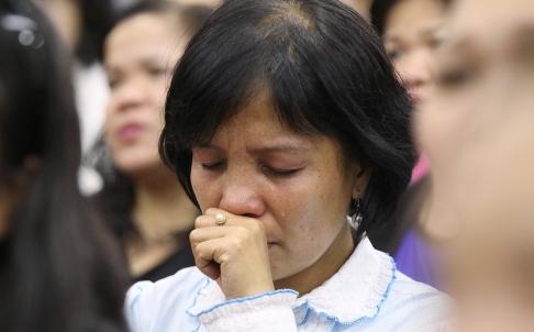Một phụ nữ tham gia lễ cầu nguyện tập thể cho các nạn nhân thiệt mạng trong siêu bão Haiyan ở Hong Kong.