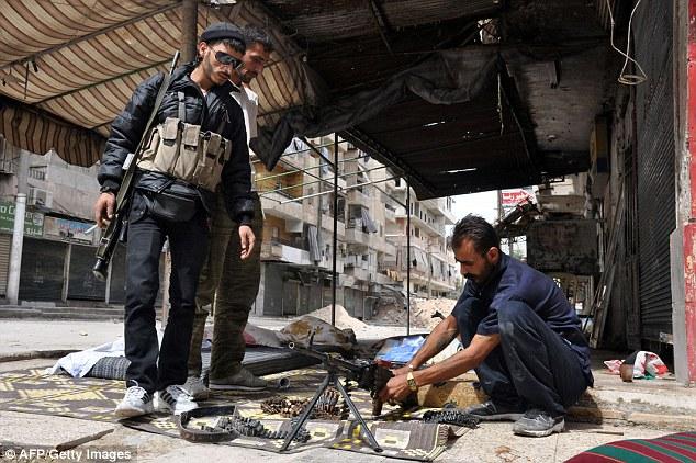 Chiến binh phiến quân vệ sinh súng trên đường phố ở Aleppo, Syria.