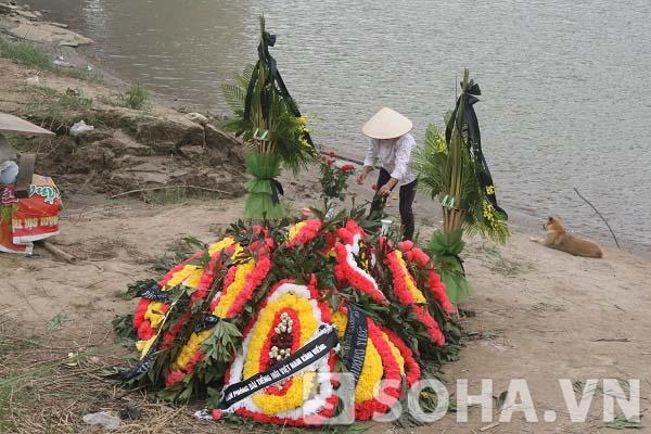 Và những bông hoa vẫn được người dân mang tới khu vực tìm kiếm thi thể chị Huyền.