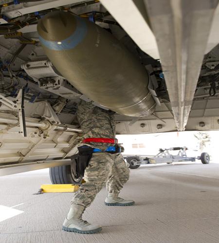 Trong ảnh là kỹ thuật viên Mỹ đang thực hiện công việc lắp quả bom vào trong khoang thân tiêm kích tàng hình hiện đại nhất thế giới F-22 Raptor.