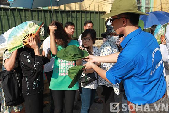 Thanh niên tình nguyện đội nắng đi phát mũ miễn phí cho người dân.