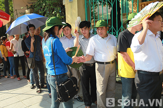 Thanh niên tình nguyện đi phát quạt và mũ tai bèo miễn phí cho người dân đến viếng.