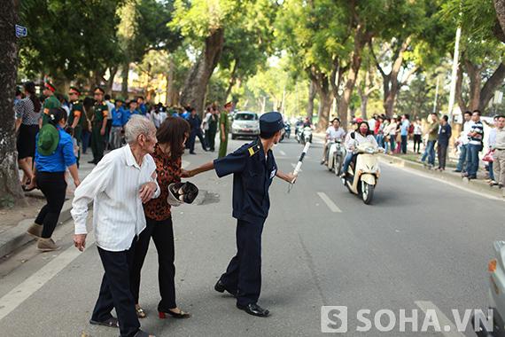 Một cán bộ trật tự giúp 2 bố con ông cụ qua đường.