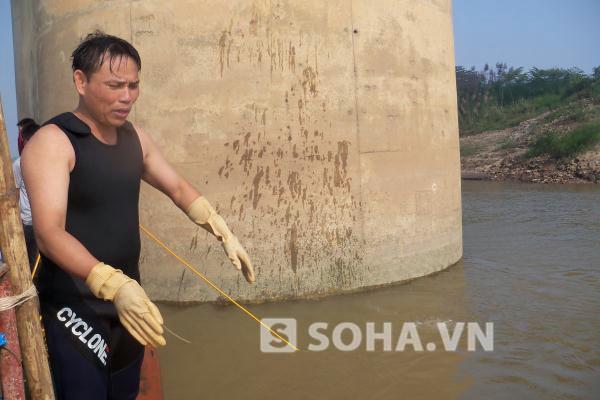 Thợ lặn chỉ nơi có nhiều đá hộc, cát dưới đáy sông...