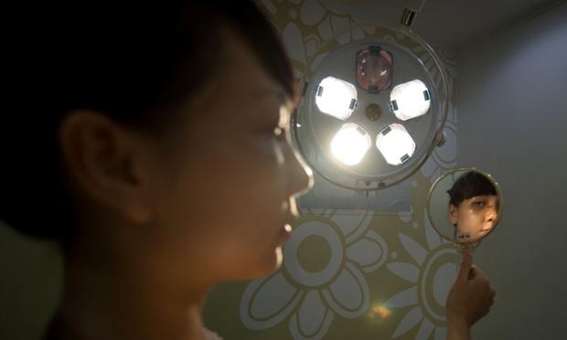 Một phụ nữ trẻ người Mỹ gốc Việt kiểm tra khuôn mặt qua gương 4 ngày sau khi phẫu thuật thẩm mỹ chỉnh mũi và mắt tại bệnh viện JK ở Seoul, Hàn Quốc.