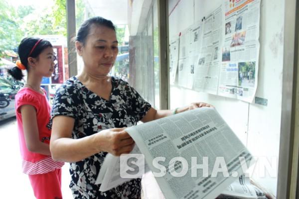 Còn bà Nguyễn Thị Mai (63 tuổi) sáng nào cũng ra đây không phải để đọc báo mà để dán báo cho mọi người đọc. Nhà bà ở Hàng Cót, hơn 1 năm nay bà nhận công việc này của bên Phường Hàng Mã dù ngày nắng hay mưa gió.