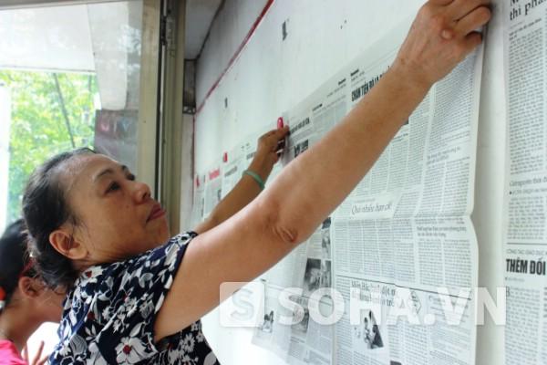 Bà Mai và cô cháu nhỏ cẩn thận dở từng tờ báo, vuốt nhẹ và dán ngay ngắn lên trang tin. Bà Mai làm công việc này không phải thu nhập ít ỏi (200 nghìn đồng/ tháng) mà vì niềm vui, thay đổi không khí.