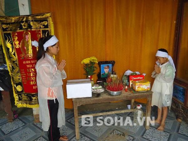 Hai con anh Sơn bên bàn thờ cha.
