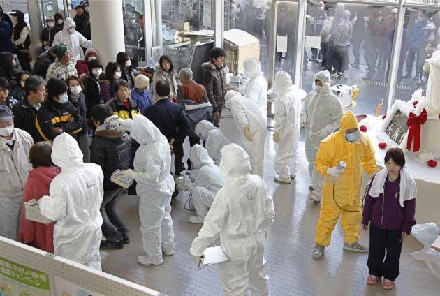 Người dân Fukushima được kiểm tra mức phóng xạ trước khi được đưa tới trung tâm cách ly