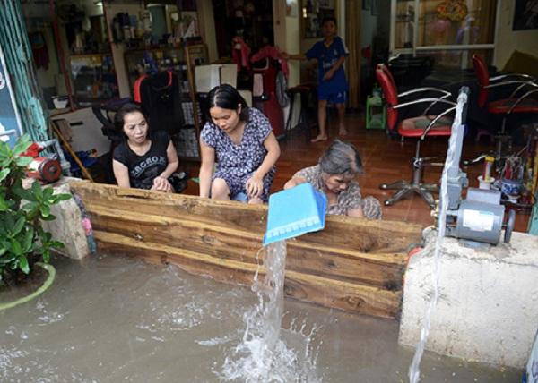 Người dân khu Định Công ngăn nước bẩn tràn vào nhà. Ảnh: Infonet