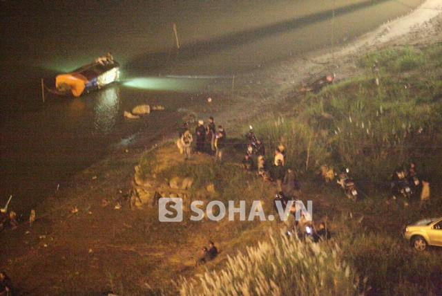 Nửa đêm nhưng rất nhiều người vẫn dõi theo ánh đèn phát ra từ những thuyền giữa sông, hay sát bờ sông tìm kiếm nạn nhân.