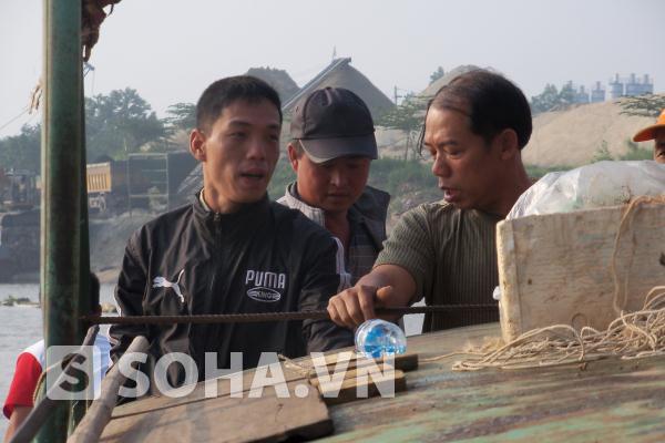 Anh Tùng (áo khoác đen, bên trái) cùng với các thành viên trong đội tìm kiếm suốt mấy ngày qua lênh đênh trên mặt sông với mong muốn sớm tìm được thi thể chị Huyền.