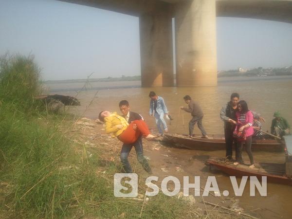 Anh Tùng bế một người phụ nữ đang trong tình trạng mệt mỏi khi tới giúp tìm kiếm thi thể vợ mình trên sông.